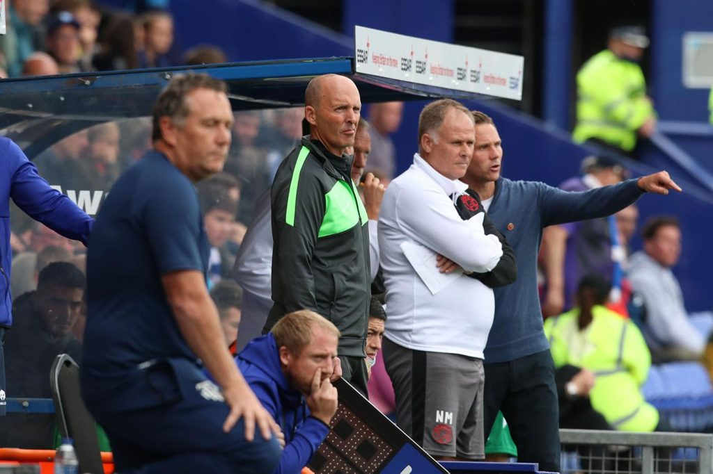 Mike Dean watches on from the technical area